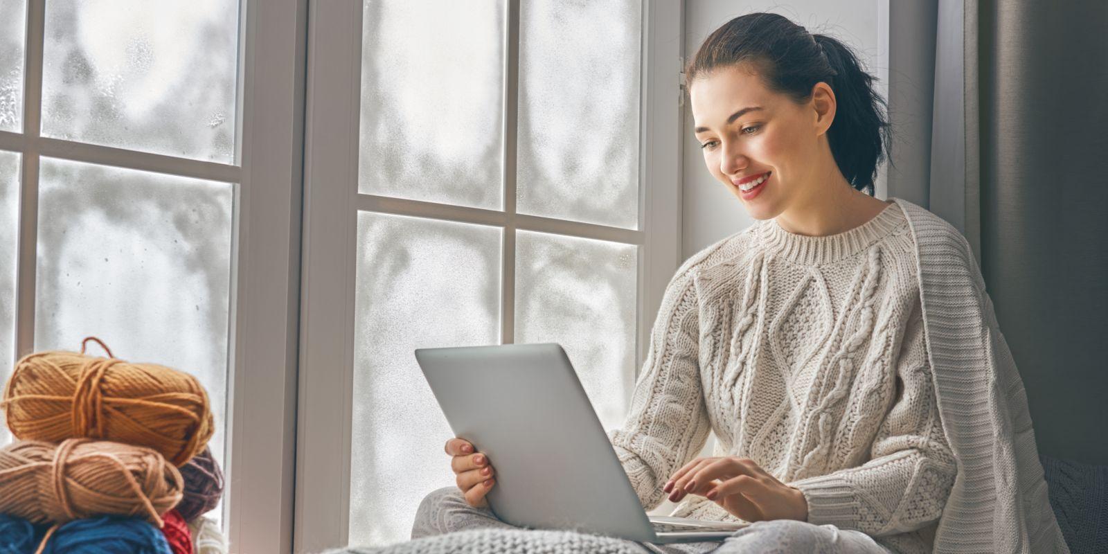 woman sitting near windows using laptop