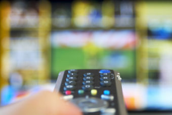 Hand holding remote with blurry tv in background