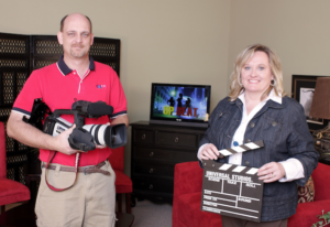 Man holding camera next to woman holding clapperboard with tv's behind them
