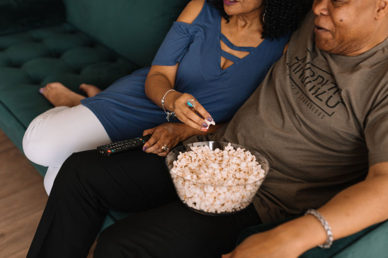 Couple sitting on couch eating popcorn