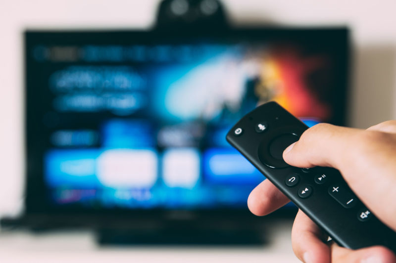 Hand holding a remote with a TV in the background