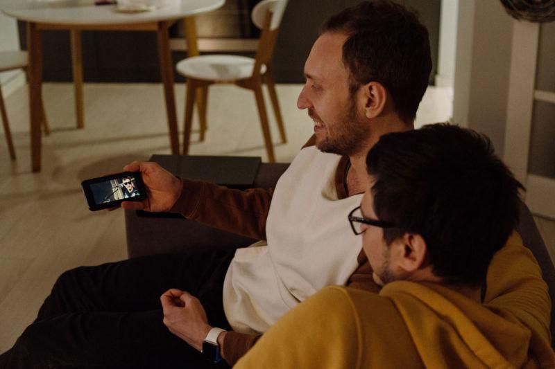 Two men watching something on phone