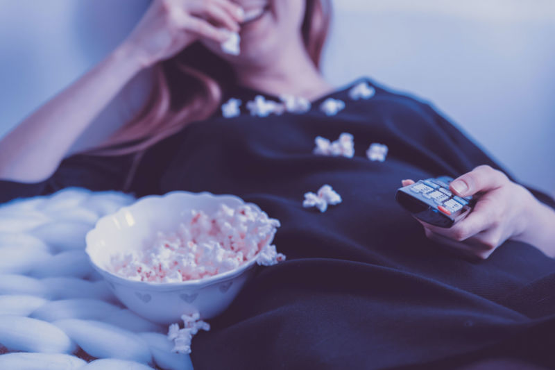 Woman eating popcorn holding remote
